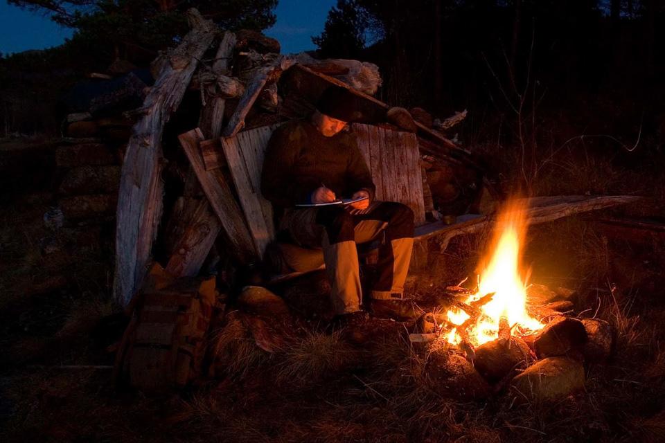 Dagens opplevelser noteres gjerne ned i turdagbok i lyset fra flammene.