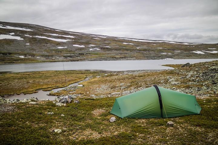 En flat og myk teltplass mellom mye steinete terreng.
