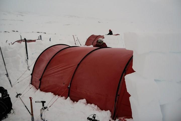 Njål legger siste finpuss på en solid levegg. Det lønner seg også med en mindre levegg foran den store for å redusere fokksnøen på teltet.