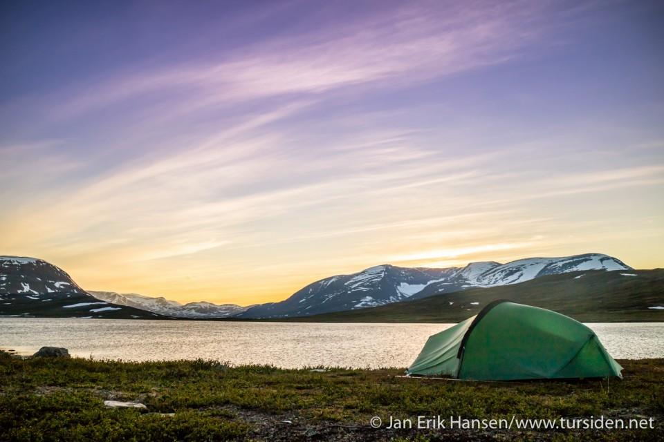 Midnattssola gir fine farger på himmelen mens den har seg en liten tur bak fjellene.