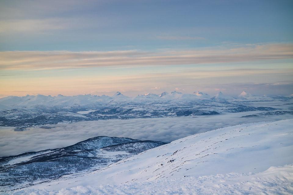 Tåke på fjorden, og toppene ytterst på Senja reiser seg i horisonten.